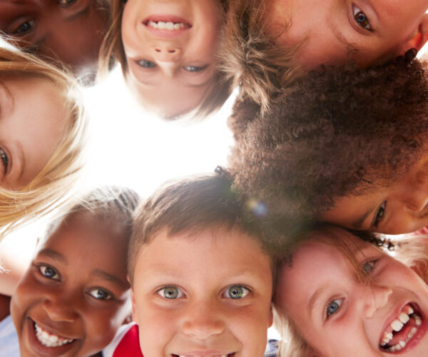 Group Of Multi-Cultural Children With Friends Looking Down Into Camera