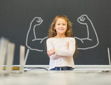 Lächelndes Mädchen in der Schule steht vor einer Tafel mit Muskeln aus Kreide