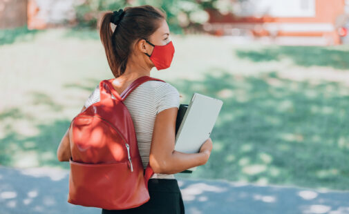 Back to school university student girl wearing covid mask walking on campus with backpack, books and laptop. Corona virus lifestyle.